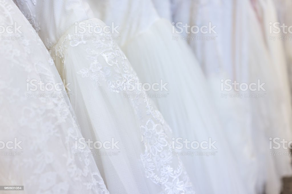 02d04a0e6b Many wedding dresses in boutique discount store, white garments hanging on  rack hangers row closeup