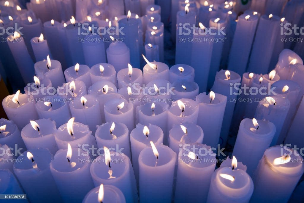 Many white candles burning. light for spirits, стоковое фото