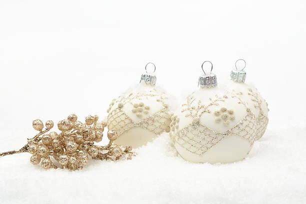 viele weiße weihnachten kugeln mit goldene dekoration im schnee - schnelles weihnachtsessen stock-fotos und bilder