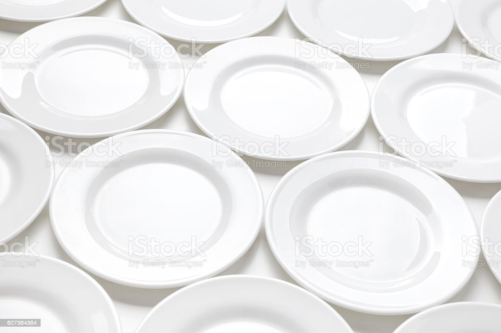 Many white plates on table, pattern of dishes stock photo