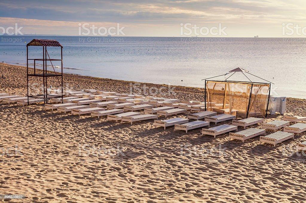 Many white sunbeds on a sandy beach. royalty-free stock photo