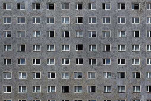 many windows on grey building facade - plattenbau