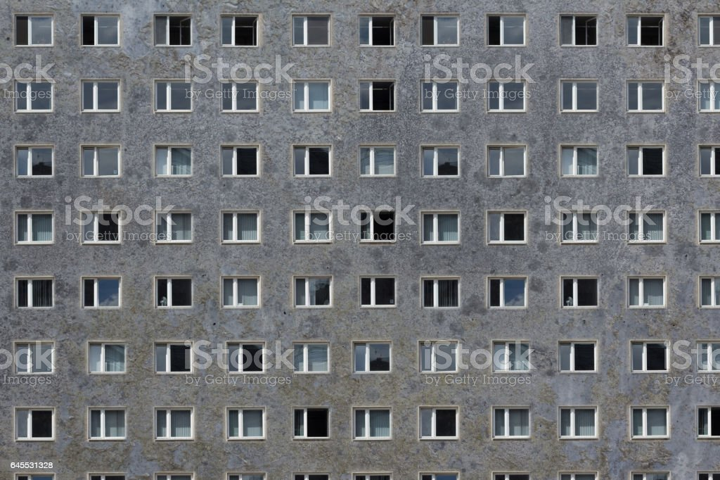 many windows on grey building facade - plattenbau stock photo