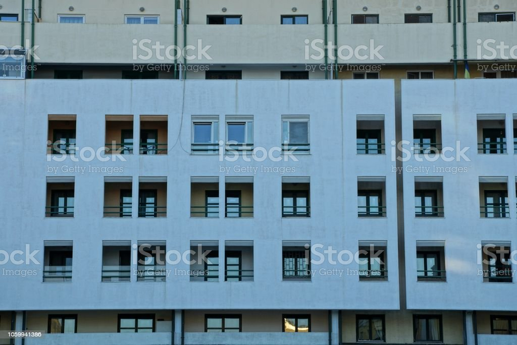 many windows on the gray concrete wall of a large house stock photo