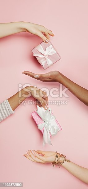 Many women hands with gifts. Abstract luxury holiday and sale concept on pink background