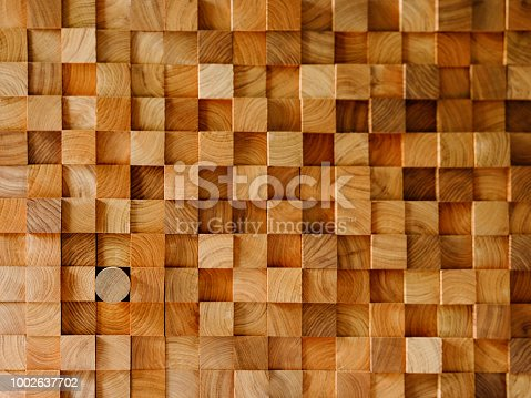istock Many wood square profiles stacked up at the same length with one round profile length within the background standing out from the crowd. 1002637702
