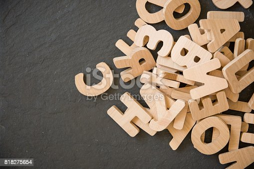 istock Many wooden letters on black background. Copy space. 818275654