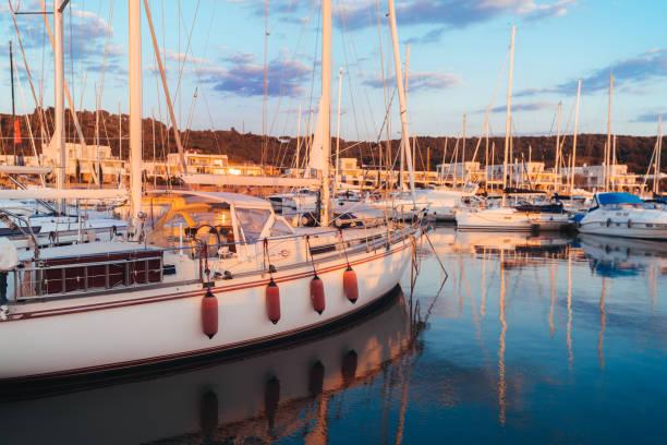 Many yachts in marina bay at sunset stock photo