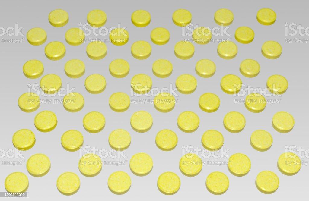 many yellow pills, arranged chequerwise