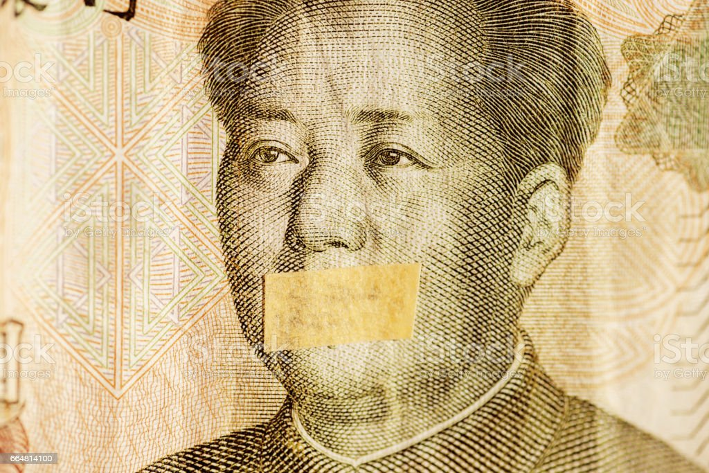 Mao portrait, leader of China with closed mouth on a banknote of Chinese Yuan, as a symbol of the instability of economy stock photo