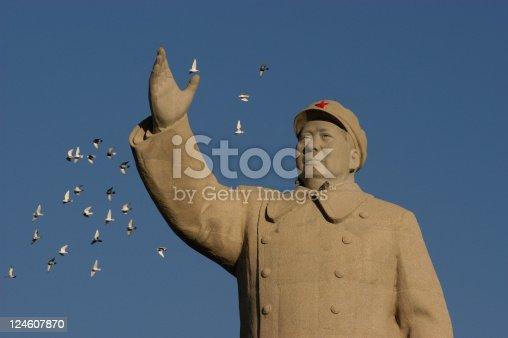 pigeons flying closeby Mao Zedong statue in Renmin Square. Kashgar (Kashi). Xinjiang Uyghur Autonomous Region. China.