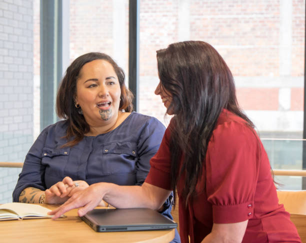 Maori and caucasian business women talking in meeting, could be coworkers, employees or management. Maori female has moko facial tattoo. stock photo