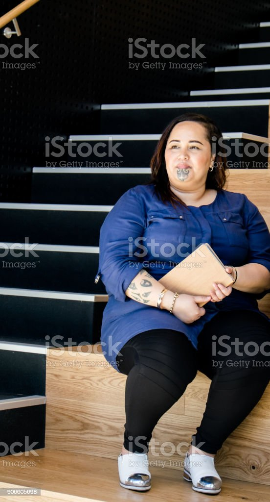 Maori business woman with moko facial tattoo sitting on steps in stair well with journal or diary, with copy space. stock photo