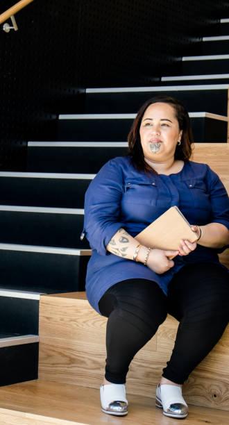 maori geschäftsfrau mit moko gesichts tattoo sitzen auf stufen treppe gut mit tagebuch, mit textfreiraum. - tribal tattoos stock-fotos und bilder