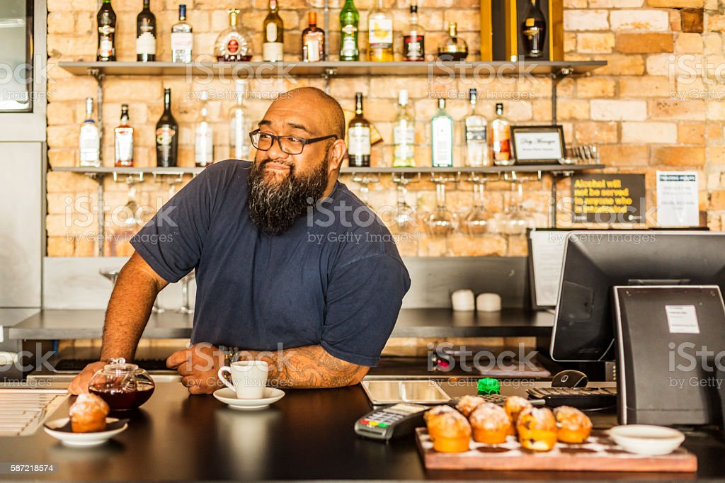 Maori Businessman Working in a New Zealand Bar or Cafe stock photo