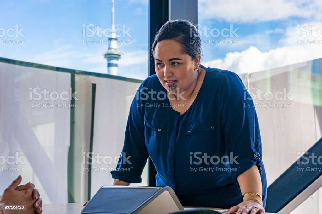 Maori Businesswoman Making a Conference Call With Auckland Skytower Behind stock photo