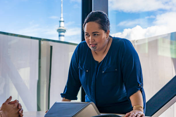 maori businesswoman making a conference call with auckland skytower behind - casual clothing stock photos and pictures