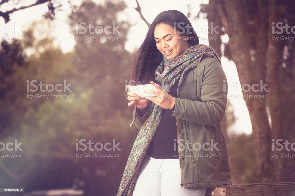 Maori girl using her smartphone. - Royalty-free 20-29 Years Stock Photo