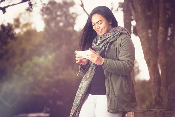 Maori girl using her smartphone. stock photo