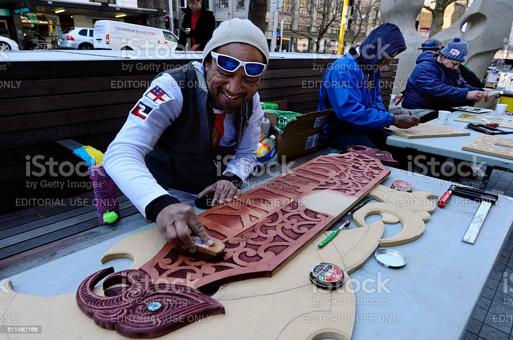 Maori man painting a Maori Wood carving stock photo