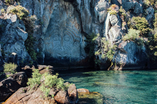 maori rock carving in cliff wall in lake taupo - maori stock photos and pictures