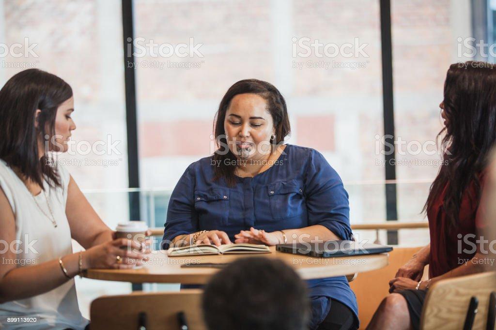 Maori woman in charge of meeting. stock photo