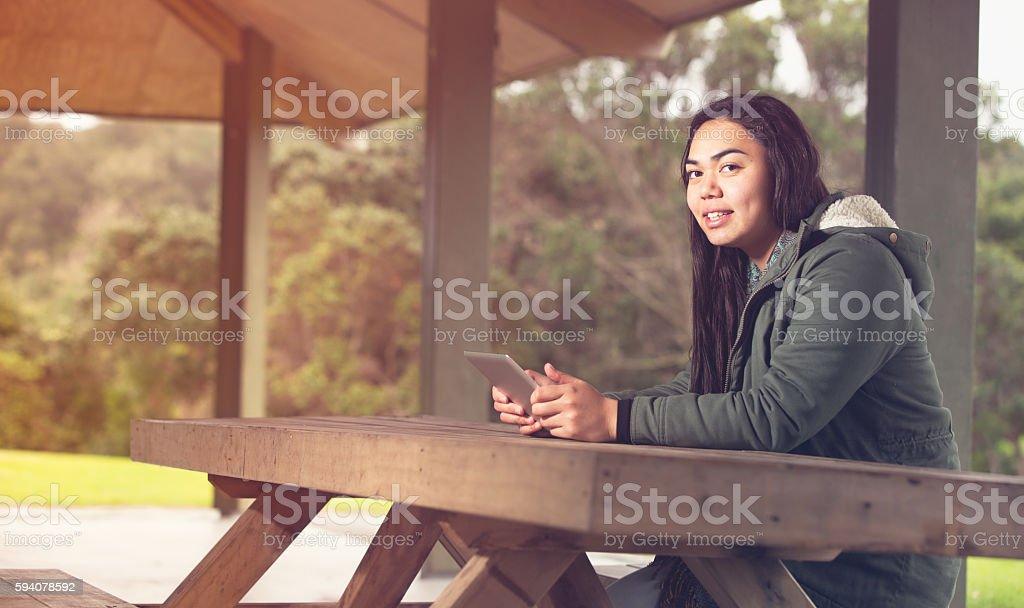 Maori young girl using tablet. stock photo