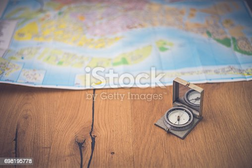 97623256istockphoto Map and compas 698195778