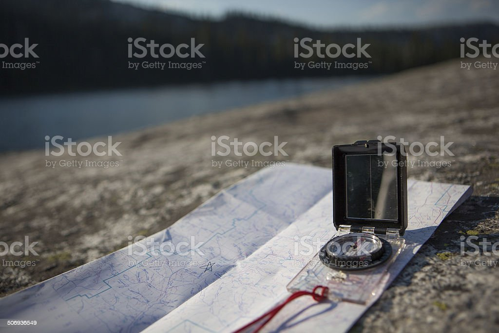 Map and Compass alongside an alpine lake. royalty-free stock photo