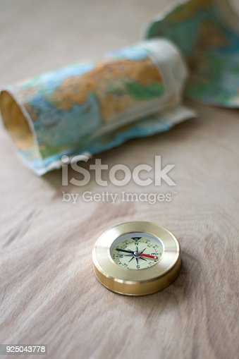 537607438istockphoto Map and compass lying on the wooden background 925043778