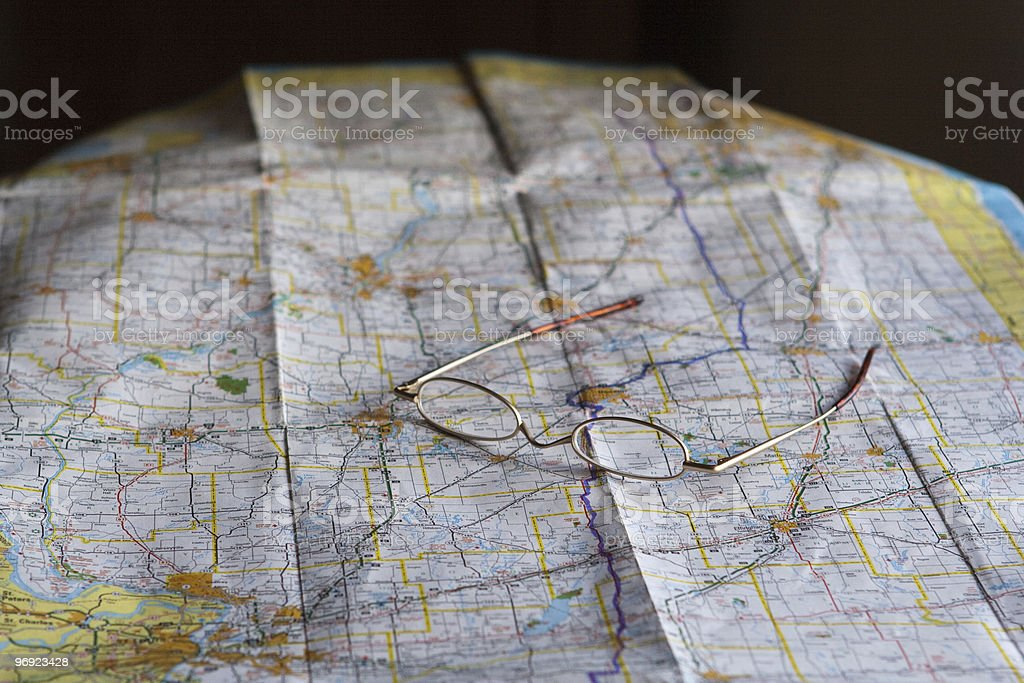 Map and reading glasses stock photo