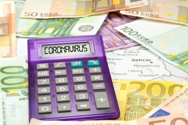Map of Germany, calculator, Euro banknotes and coronavirus stock photo