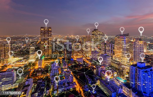 Map pin flat of city, global business and network connection in futuristic technology concept in Asia. Skyscraper and high-rise buildings at night in Bangkok Downtown, Thailand.