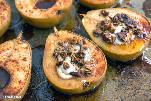 Baked d'anjou pears filled with granola and yogurt, sprinkled with cinnamon, and drizzled with maple syrup
