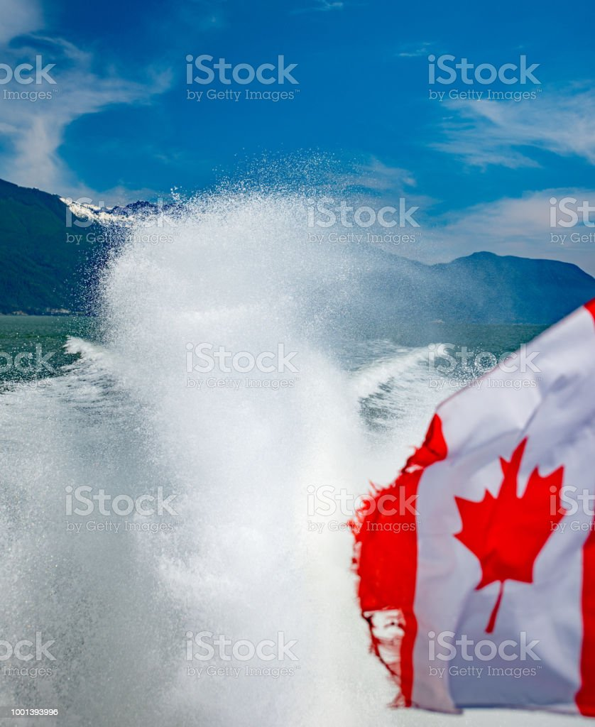 Maple leaf flag on boat captured with propulsion jet of water behind flag stock photo