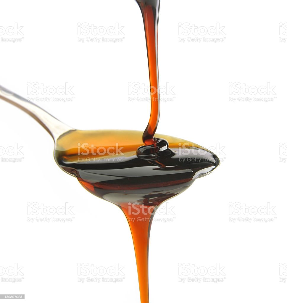 Maple syrup being poured onto a spoon and dripping off stock photo