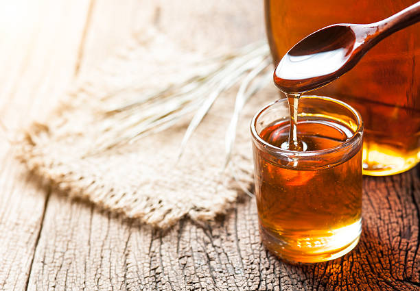maple syrup in glass bottle on wooden table - maple syrup stock photos and pictures