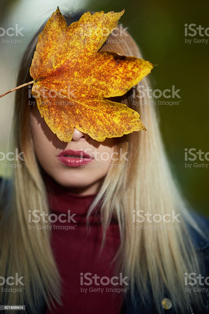 maple tree leaf on woman face stock photo