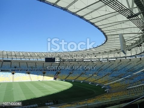 Interior view of the Maracana Stadium. An impressive stadium located in the city of Rio de Janeiro (Brazil). Blue and yellow chairs, green soccer field and blue sky with detail of the structures.