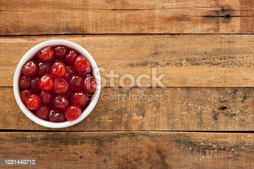 Top view of white bowl full of maraschino cherries over wooden table