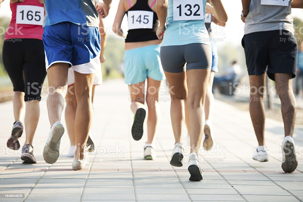 Marathon. Marathoners running. A large group of legs in a walking race with a pavement foreground. 10000 Meter Stock Photo