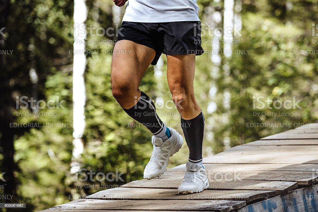 marathon runner running in forest stock photo
