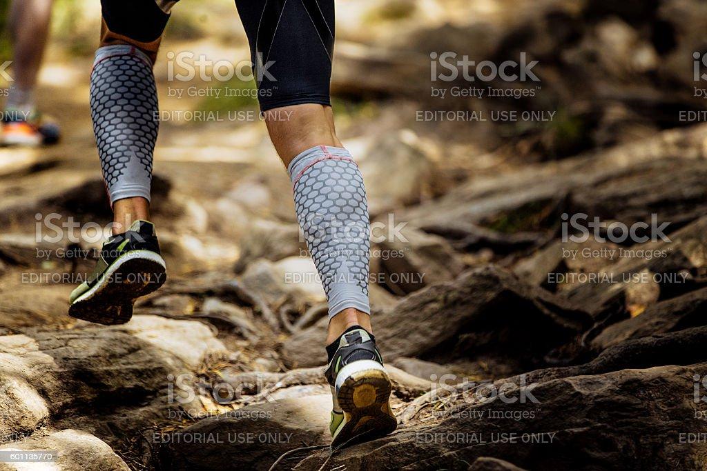 marathon runner running rocks in mountain stock photo