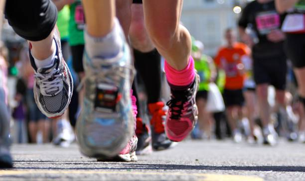 marathon runners close up legs and shoes - marathon stock photos and pictures