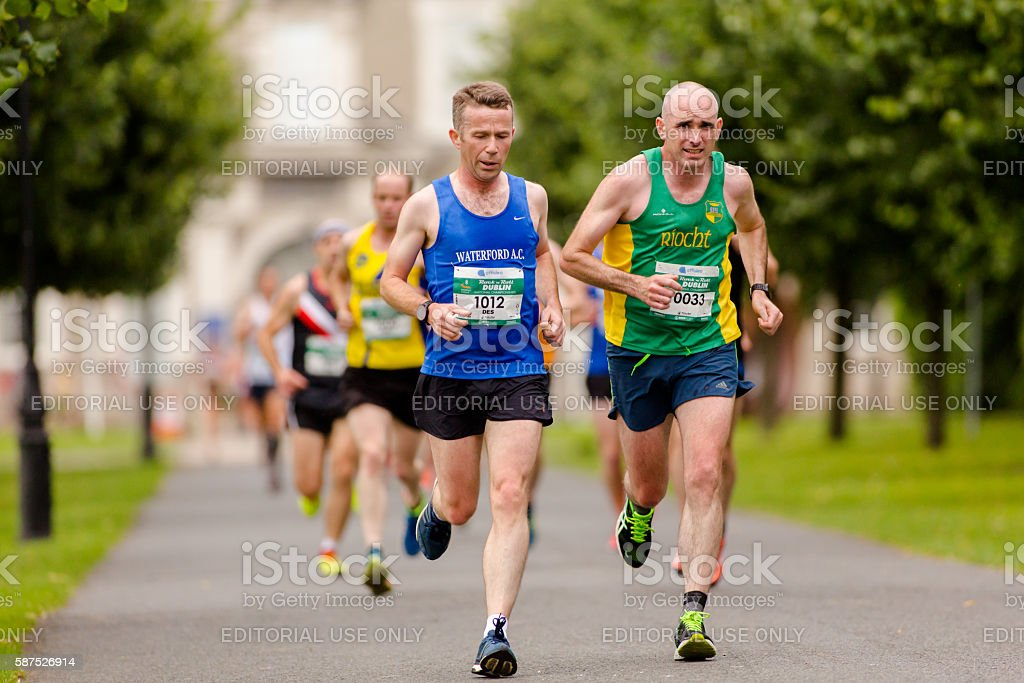 Marathon runners competing side by side stock photo