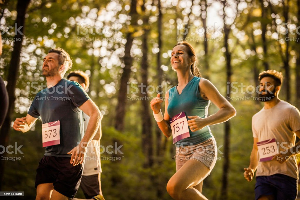 Marathon runners having a race through the forest. - Royalty-free Adult Stock Photo