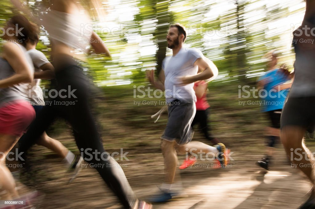Marathon runners in blurred motion running through the forest. stock photo