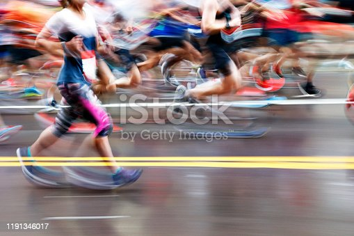 The blurred motion of a group of marathon runners as they run on an urban street.