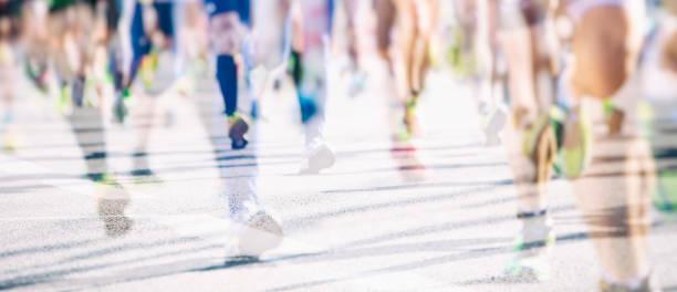 corredores de maratón en el fondo de la ciudad - maratón fotografías e imágenes de stock