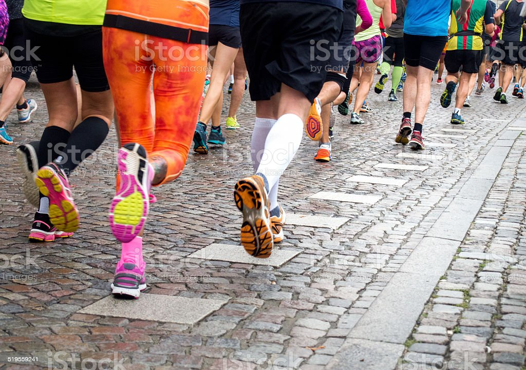 Marathon Runners running athletes at a marathon, back view 10000 Meter Stock Photo